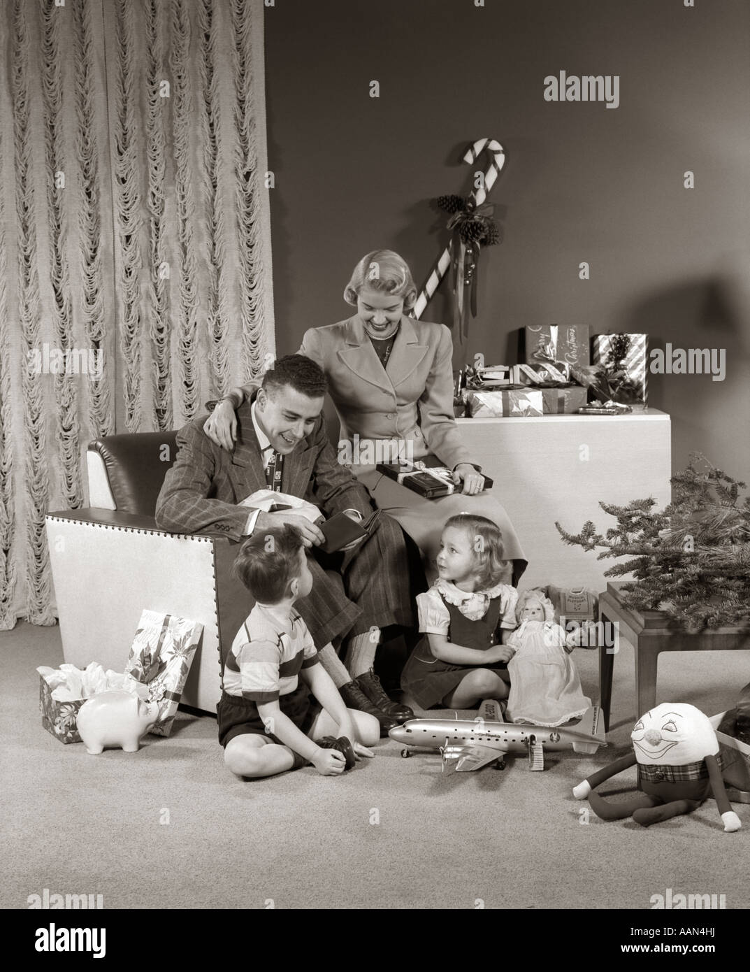 1940s 1950s family opening christmas presents stock image - 1950s Christmas