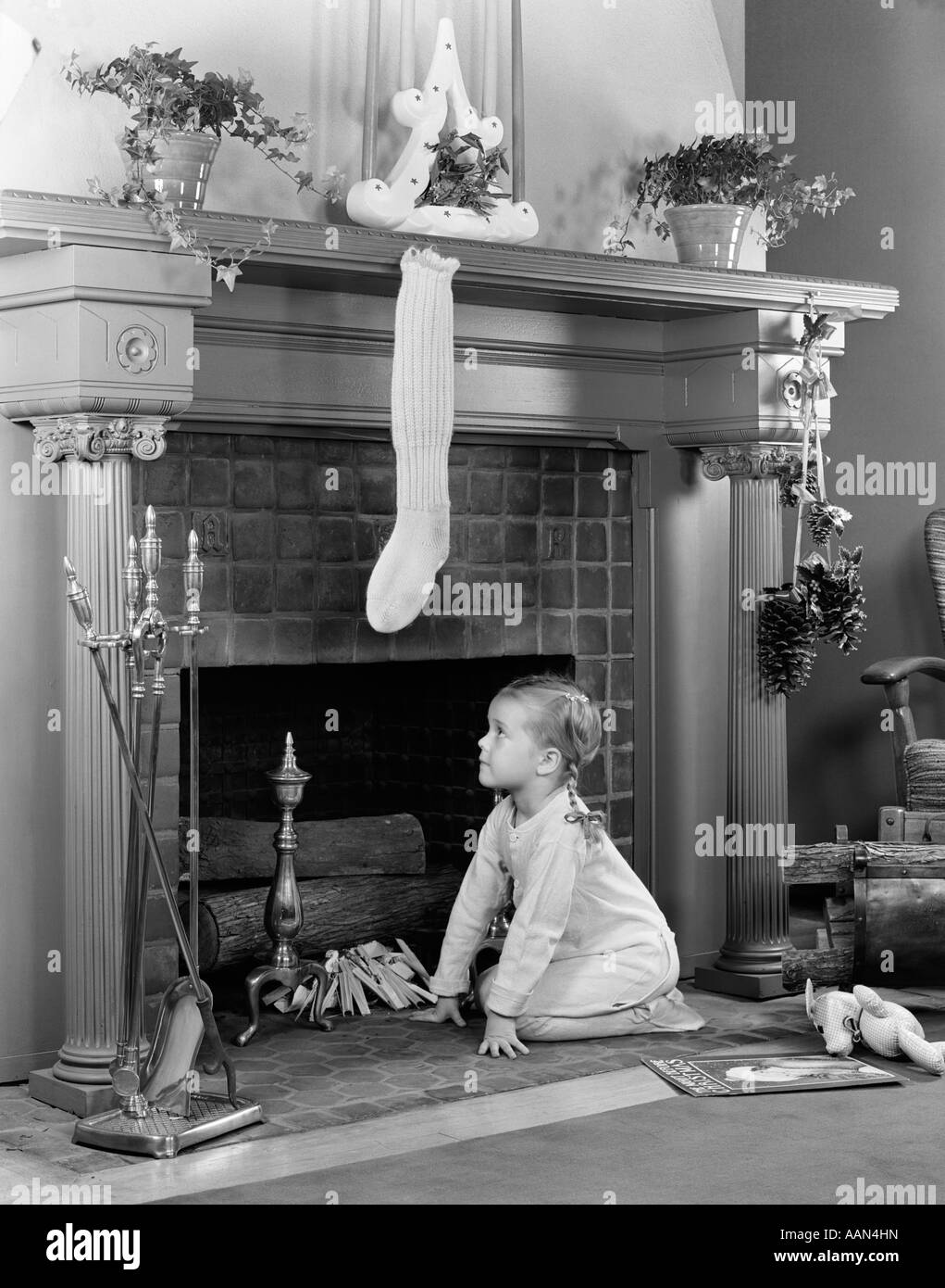 1940s LITTLE GIRL IN PAJAMAS KNEELING BY FIREPLACE UNDER STOCKING WAITING FOR SANTA CLAUS - Stock Image