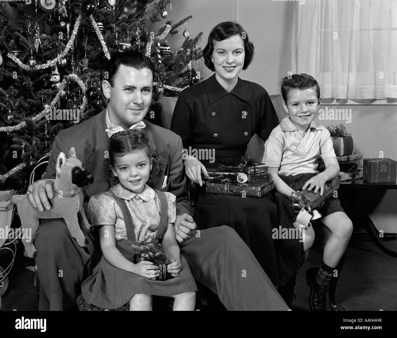 1940s 1950s Family Sitting Around Christmas Tree Holding