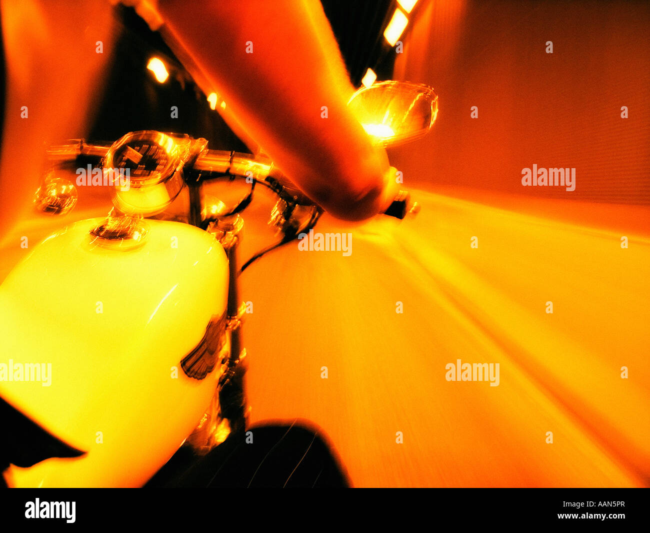 Riding a motorbike at night under artificial light - Stock Image