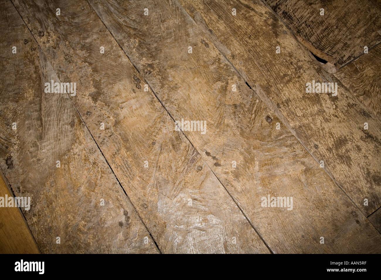 Worn old 15th century oak floorboards in manor house Treowen Wales UK Stock Photo