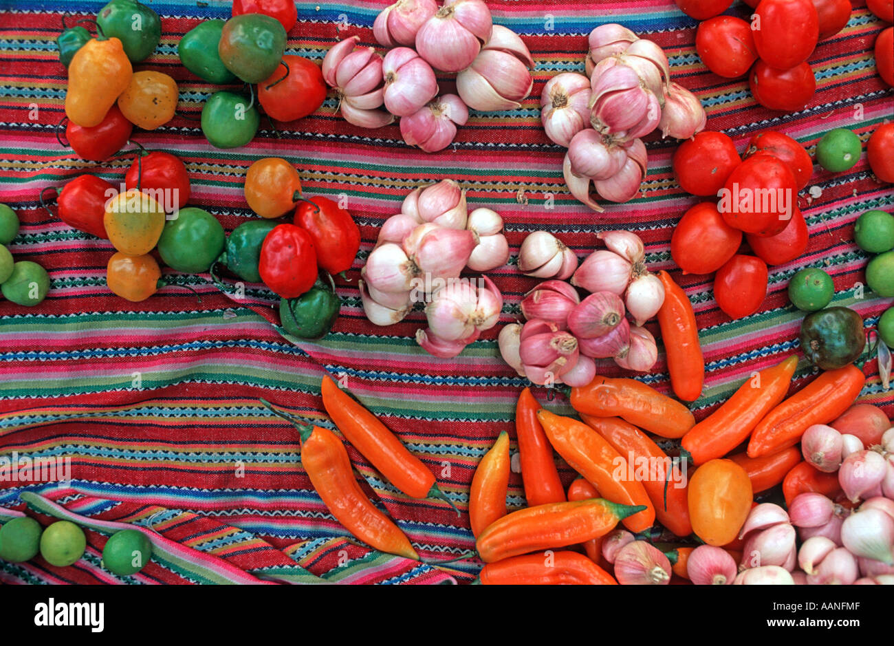 Selection of garlic citrus fruit chilli peppers and other capsicums laid out on a colourful woven Peruvian textile Huaraz N Peru - Stock Image