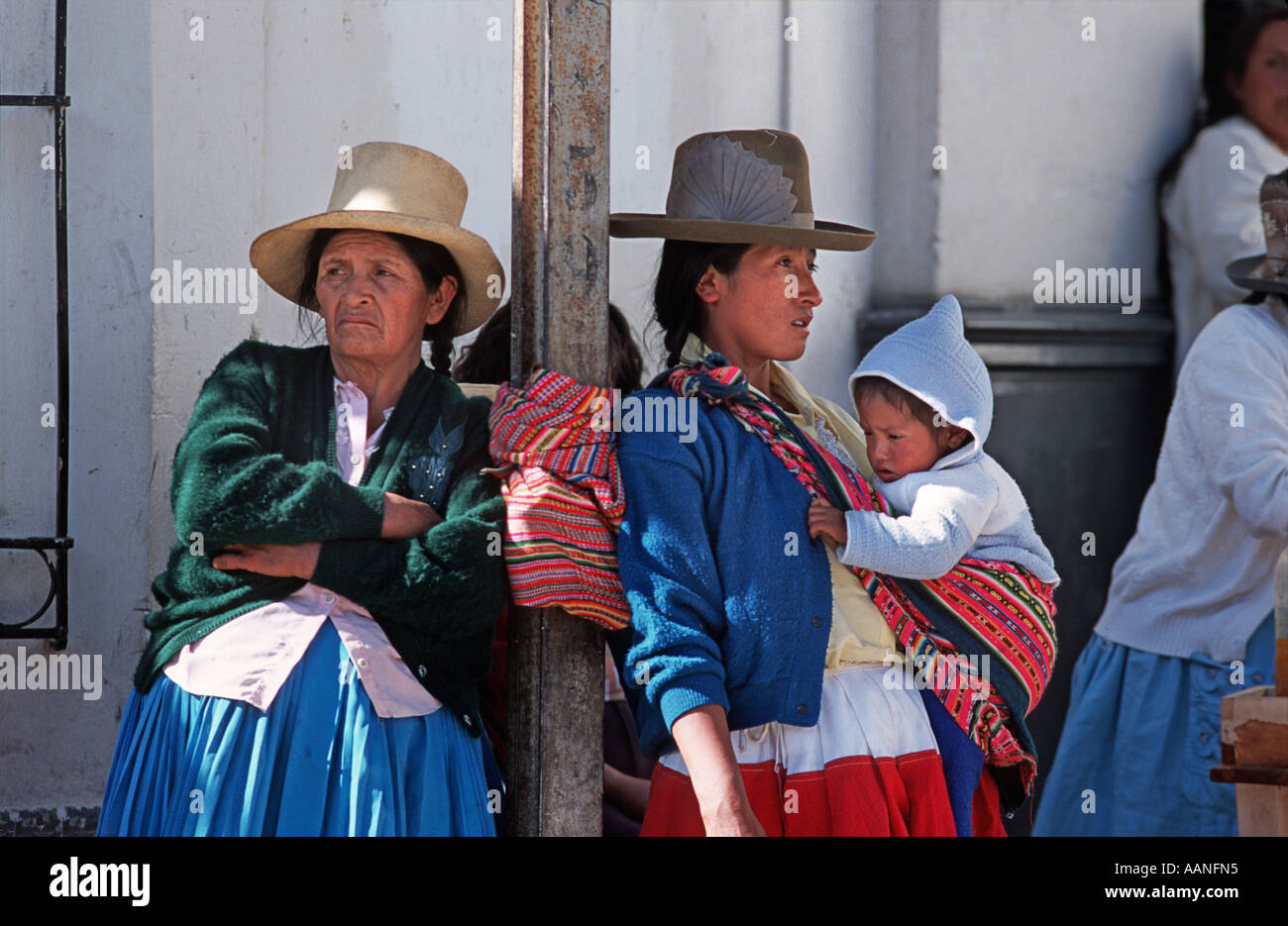 Women one carrying child standing on a street corner during local festivities Calleyon de Huaylas Northern Peru - Stock Image
