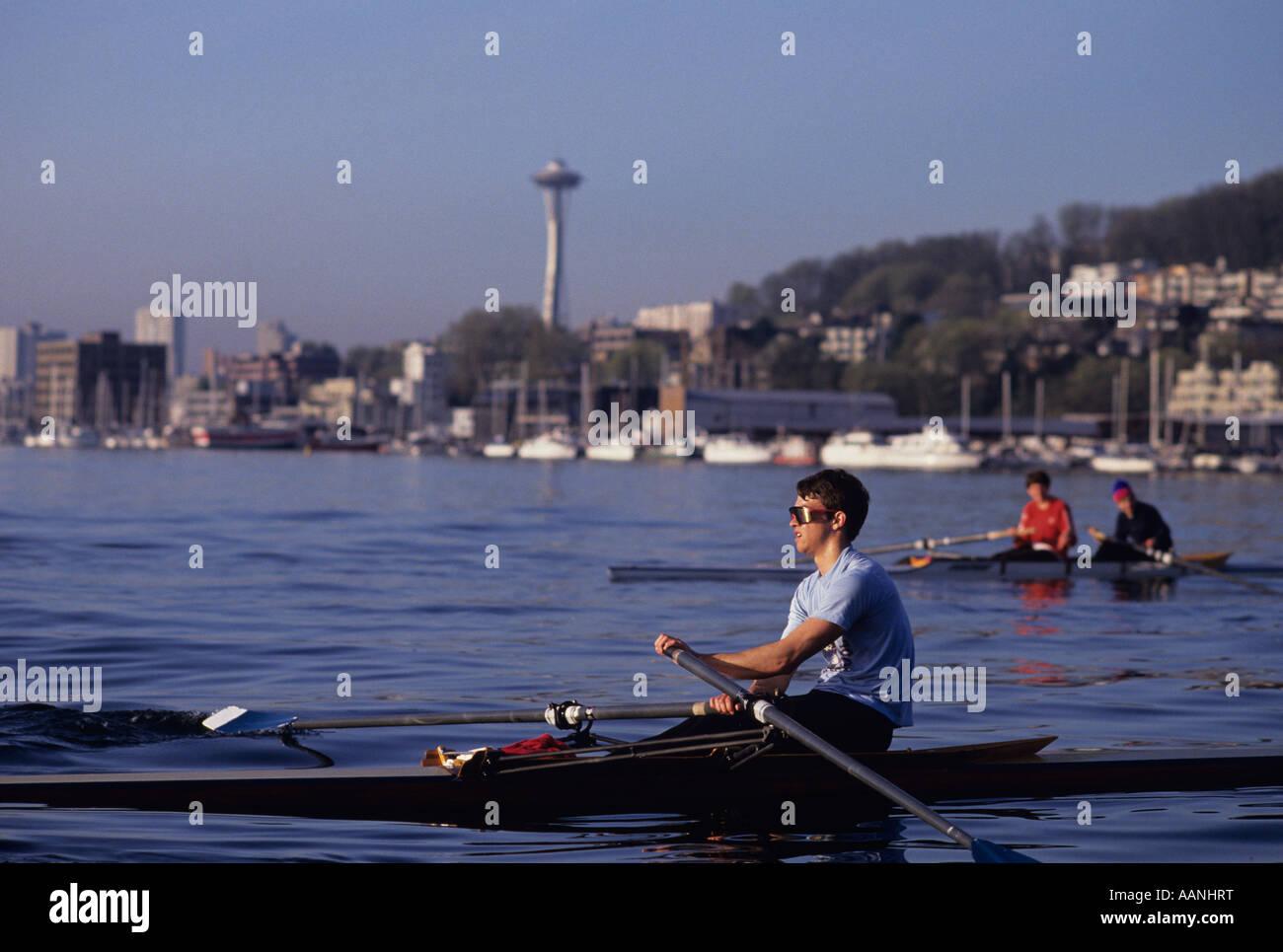 Single and two man shell with men rowing on Lake Union at sunrise, Seattle, Washington State - Stock Image