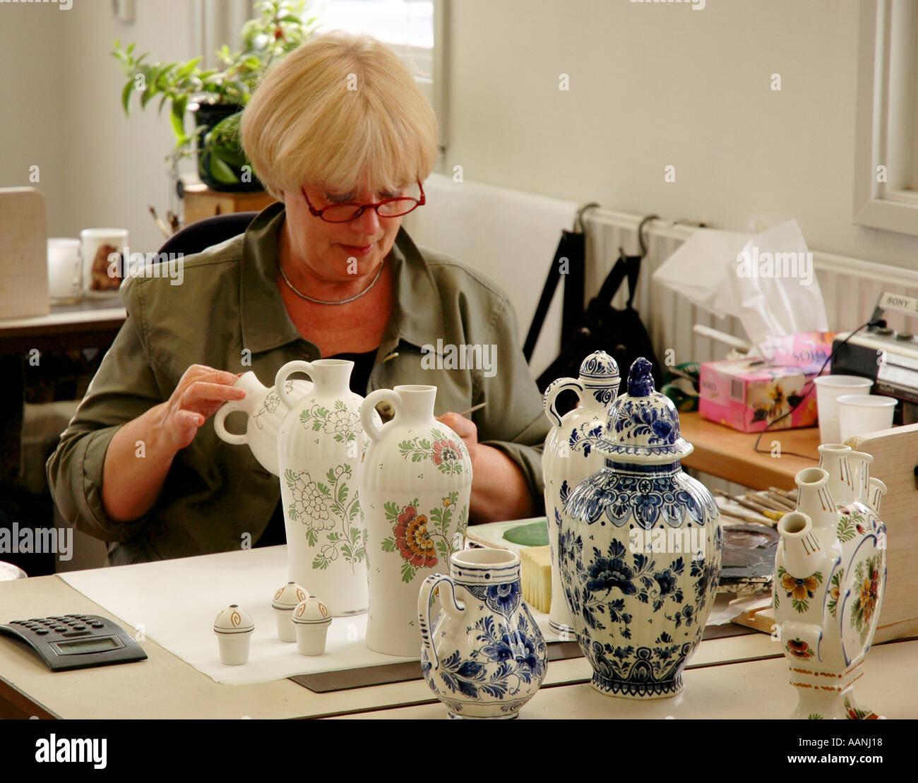 Delft, Holland Artist hand painting traditional dutch blue pottery De Delftse Pauw manufacturer location near Amsterdam, Holland - Stock Image