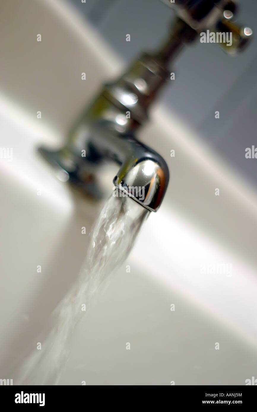 close up shot of water running from old fashioned type of tap faucet - Stock Image