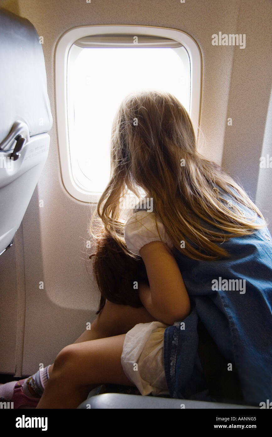 Little girl with doll looking out of airplane window Stock Photo