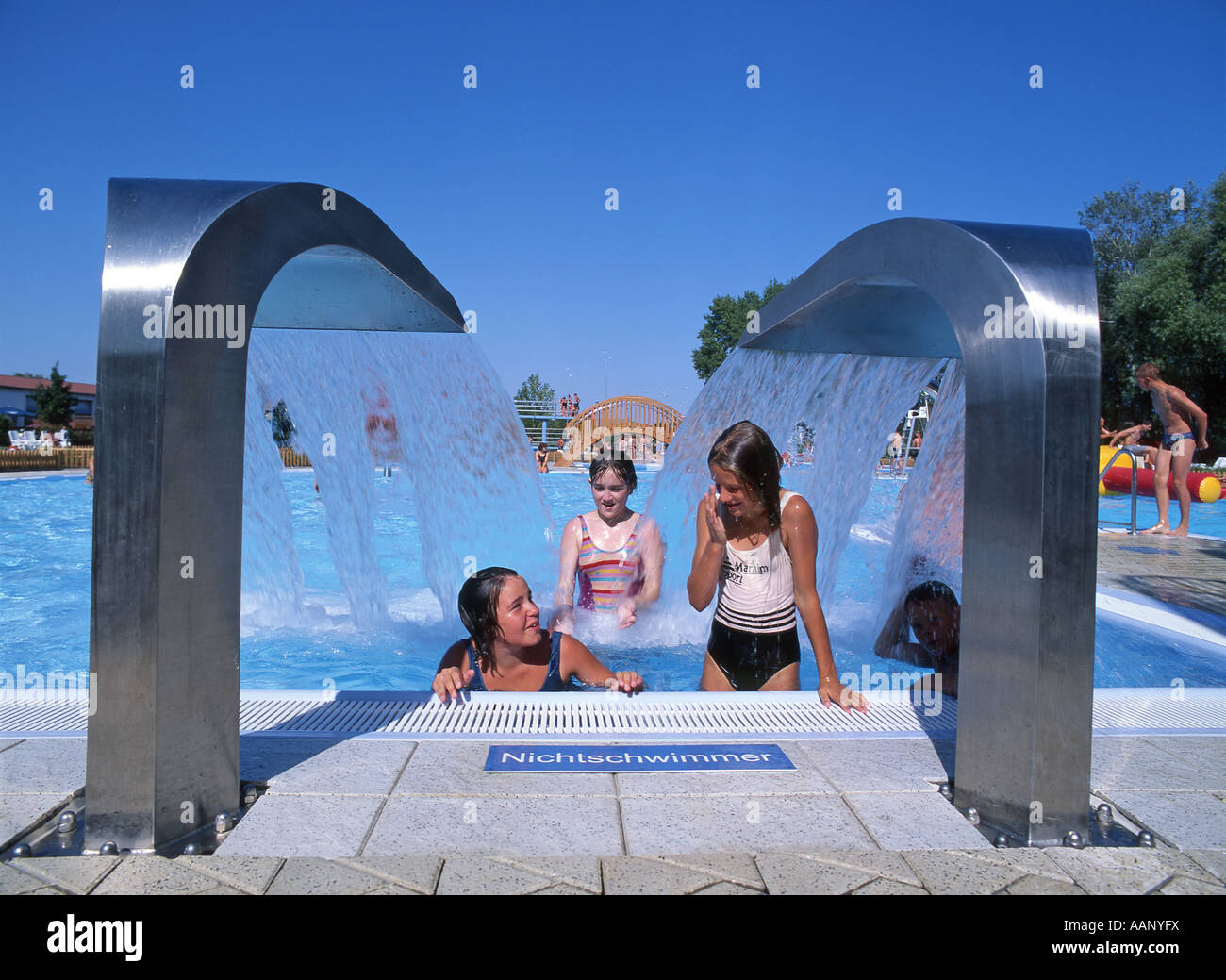 girls and waterspouts in open-air swimming pool, Germany ...