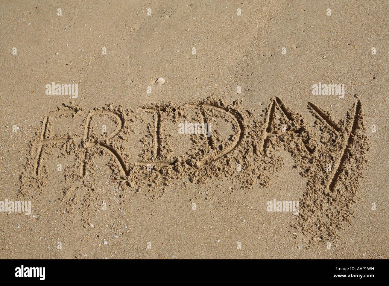 friday written on sand, weekdays - Stock Image