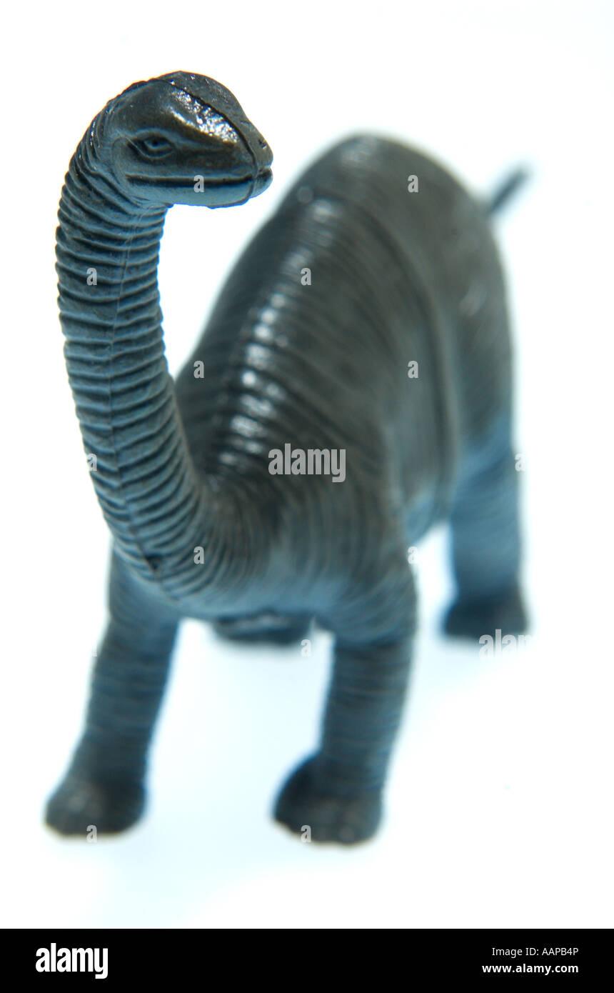 still life of minature toy model dinosaur Brontasaurus extinct obsolete - Stock Image