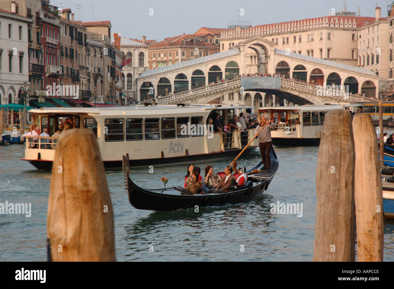 Late afternoon sun on a gondola and vaporetto water buses on the Grand Canal near the Rialto Bridge Venice. - Stock Image