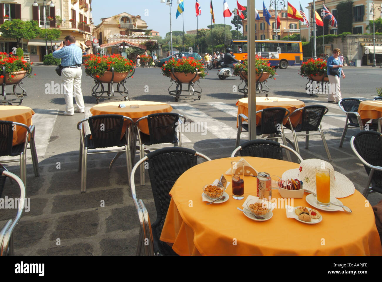 Sorrento resort Tasso Square pavement bar table with drinks and nuts with floral display tourist traffic and flags flying - Stock Image