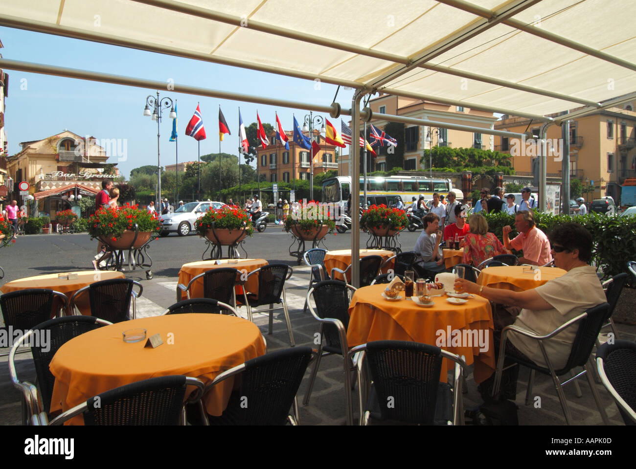 Sorrento resort Tasso Square tourists at pavement bar tables with drinks floral display traffic and flags flying - Stock Image