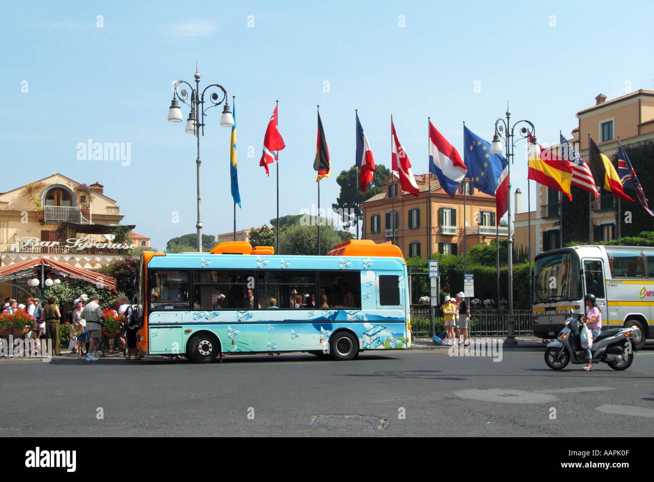Sorrento resort town centre Tasso Square with bus stop and traffic with flags flying - Stock Image
