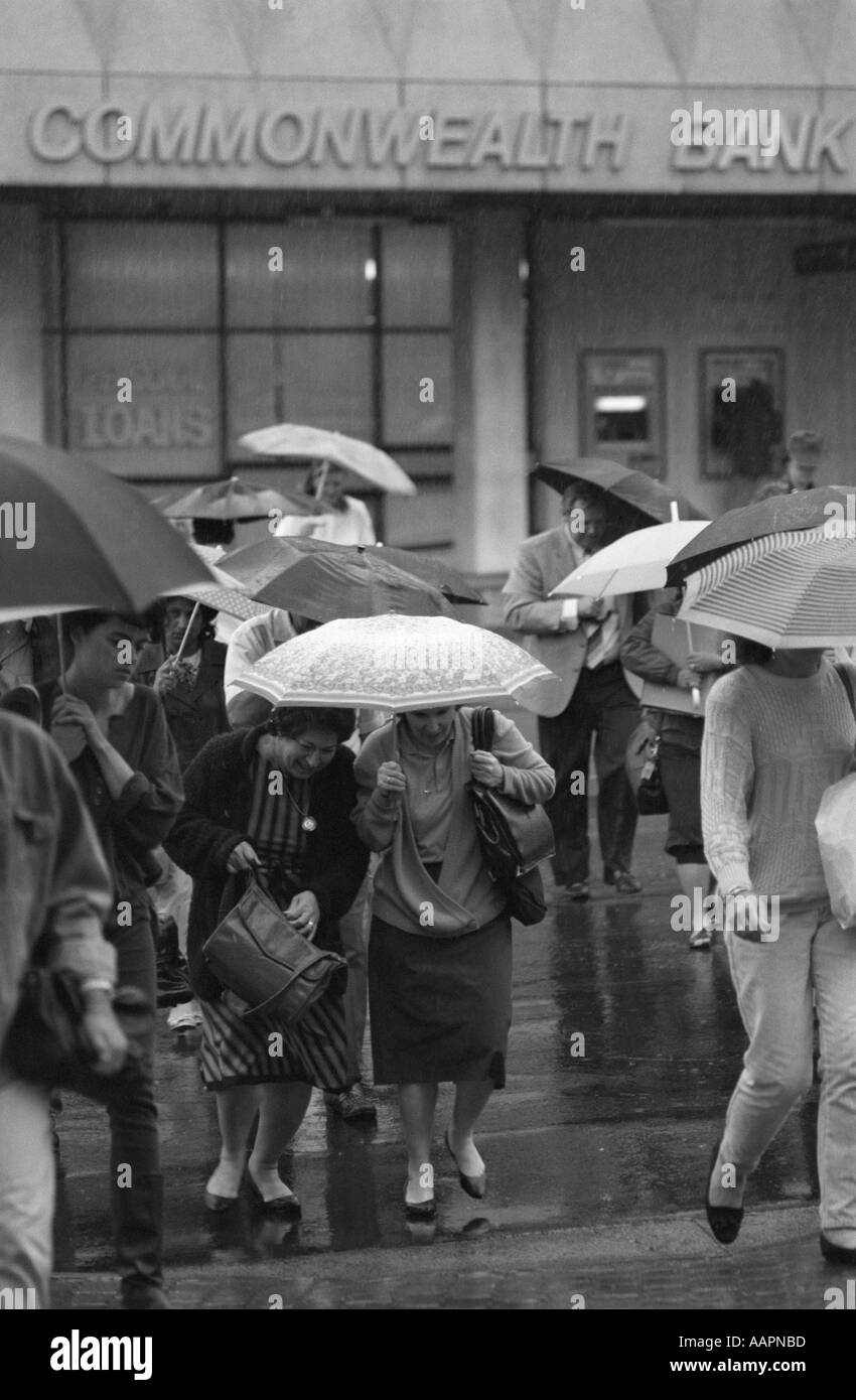 People with umbrellas in heavy rain crossing street by Commonwealth Bank, Sydney city centre, Australia. 1987 - Stock Image