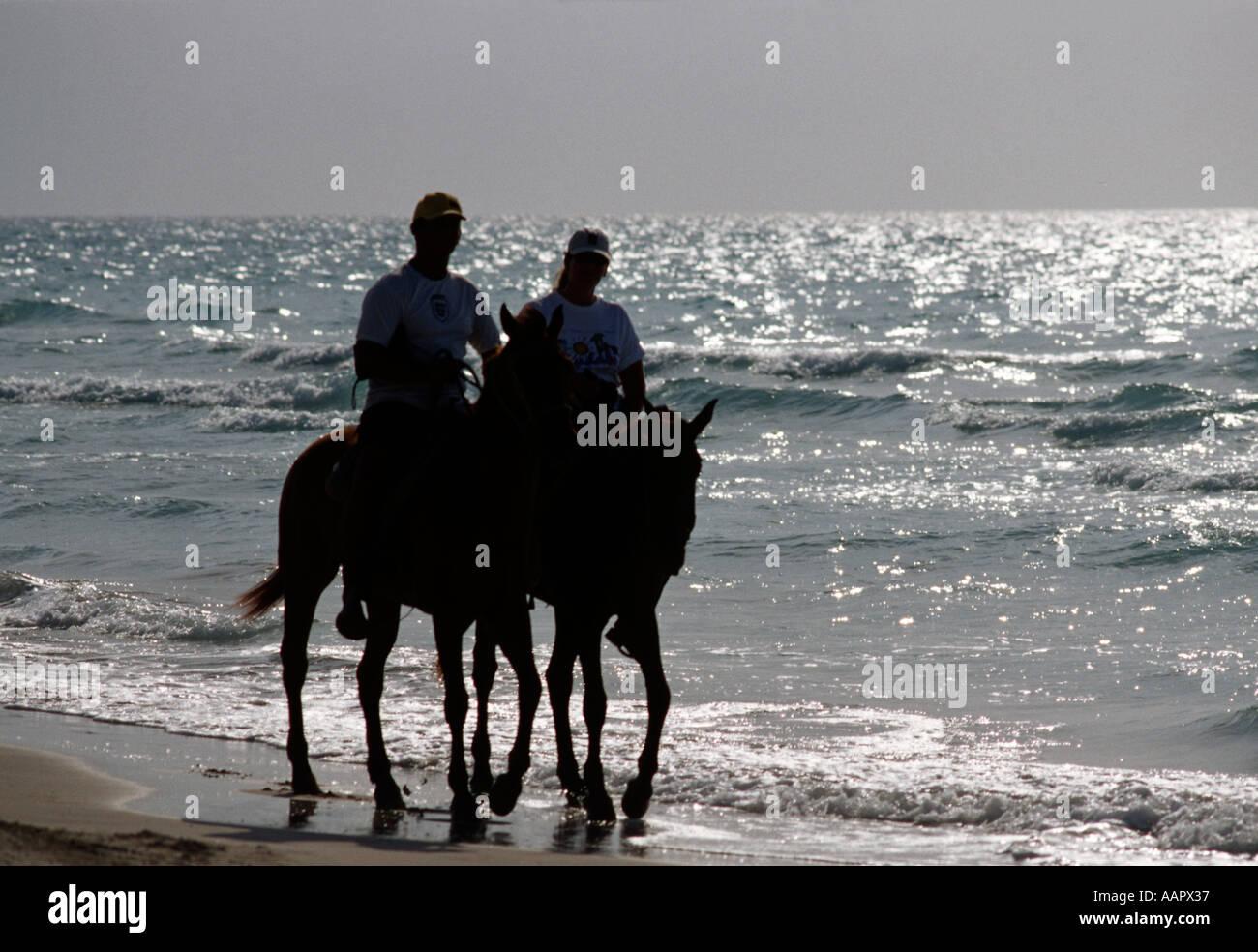 Couple riding horses along the shore at Jibacoa beach Cuba Stock Photo