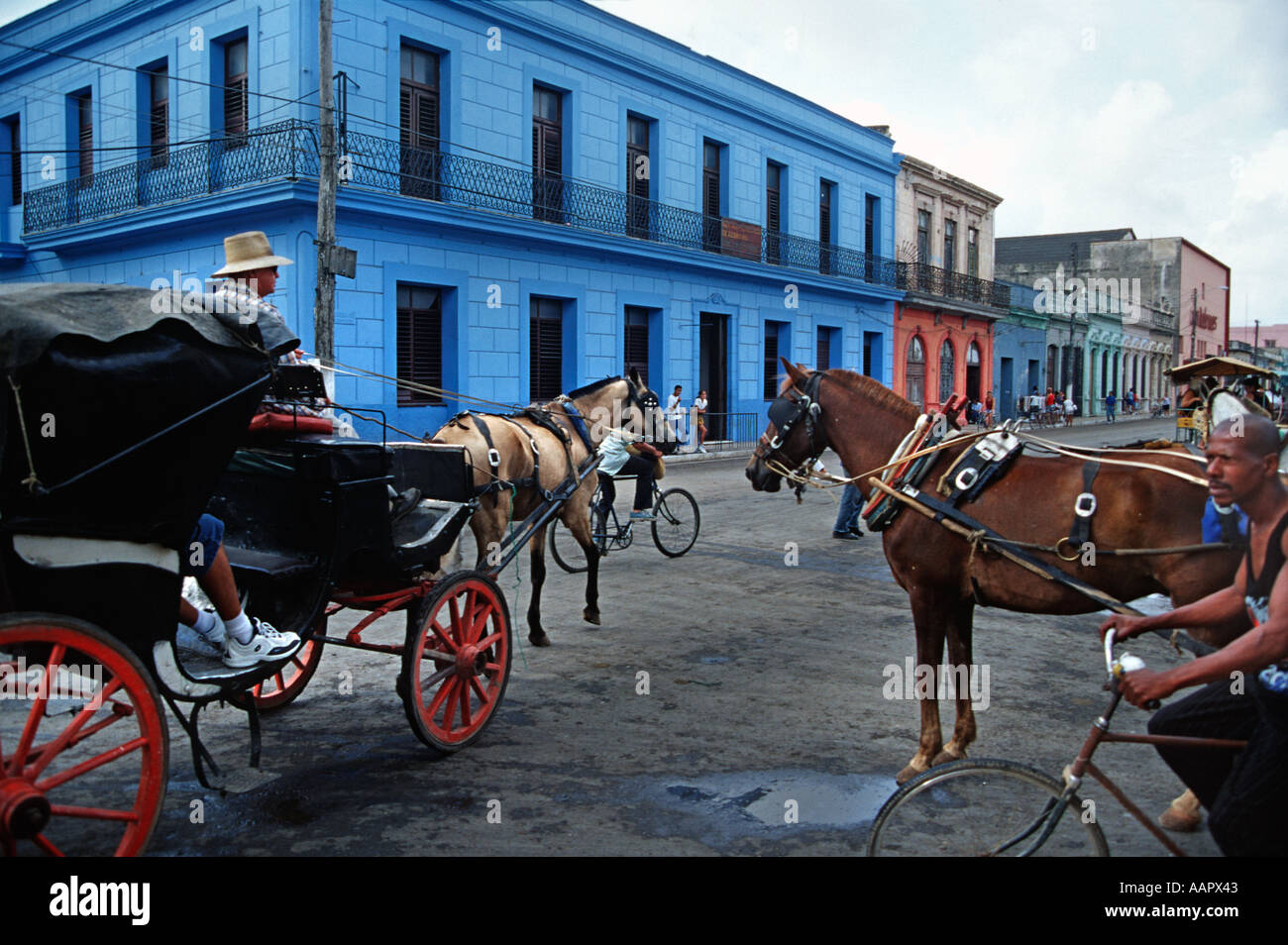 Street scene in Cardenas Cuba Man on bicycle and horse drawn carriages in the street Colonial buildings - Stock Image
