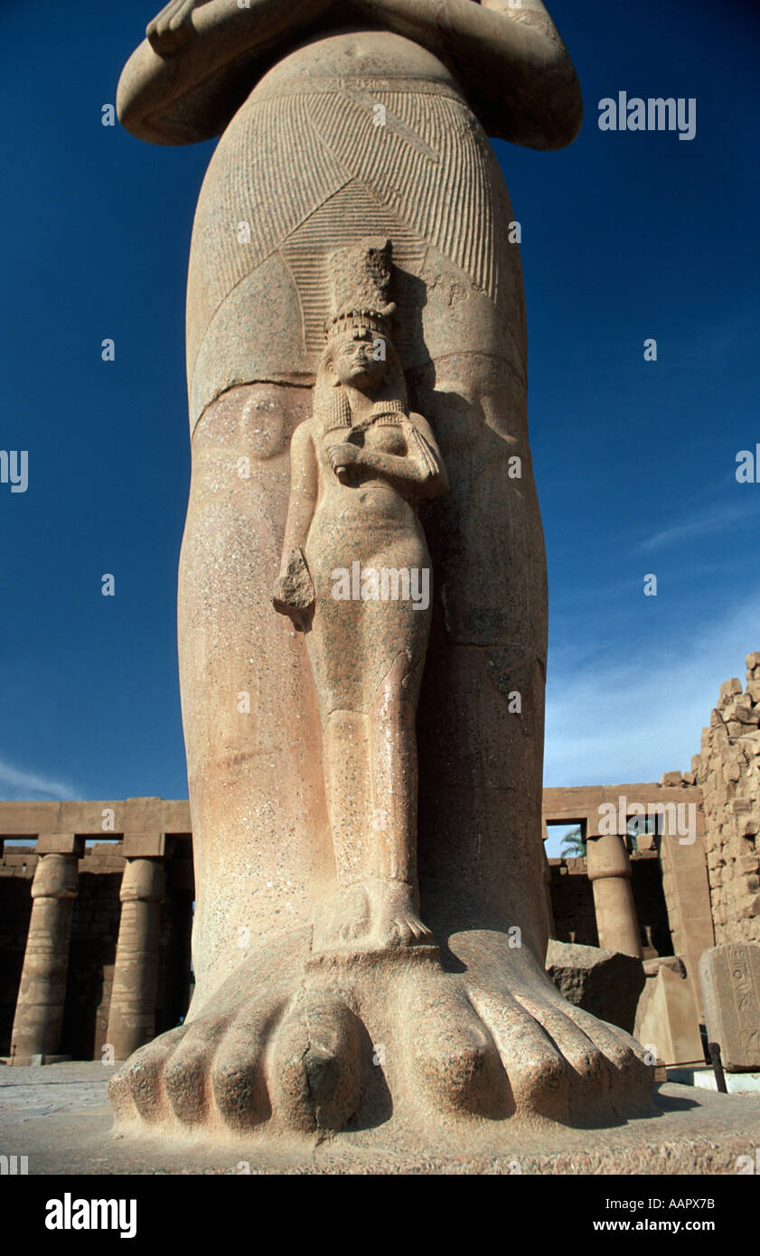 Luxor statue of consort of Ramses II at his feet Karnak Temple Luxor Egypt - Stock Image