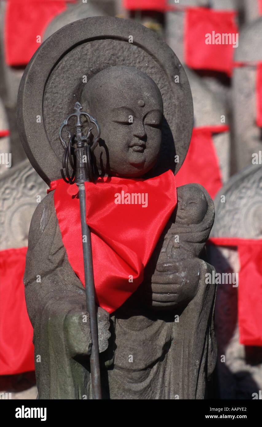 Stone carved Misu Jizo statues with red bib and holding a baby child Taima Nara prefecture Japan - Stock Image