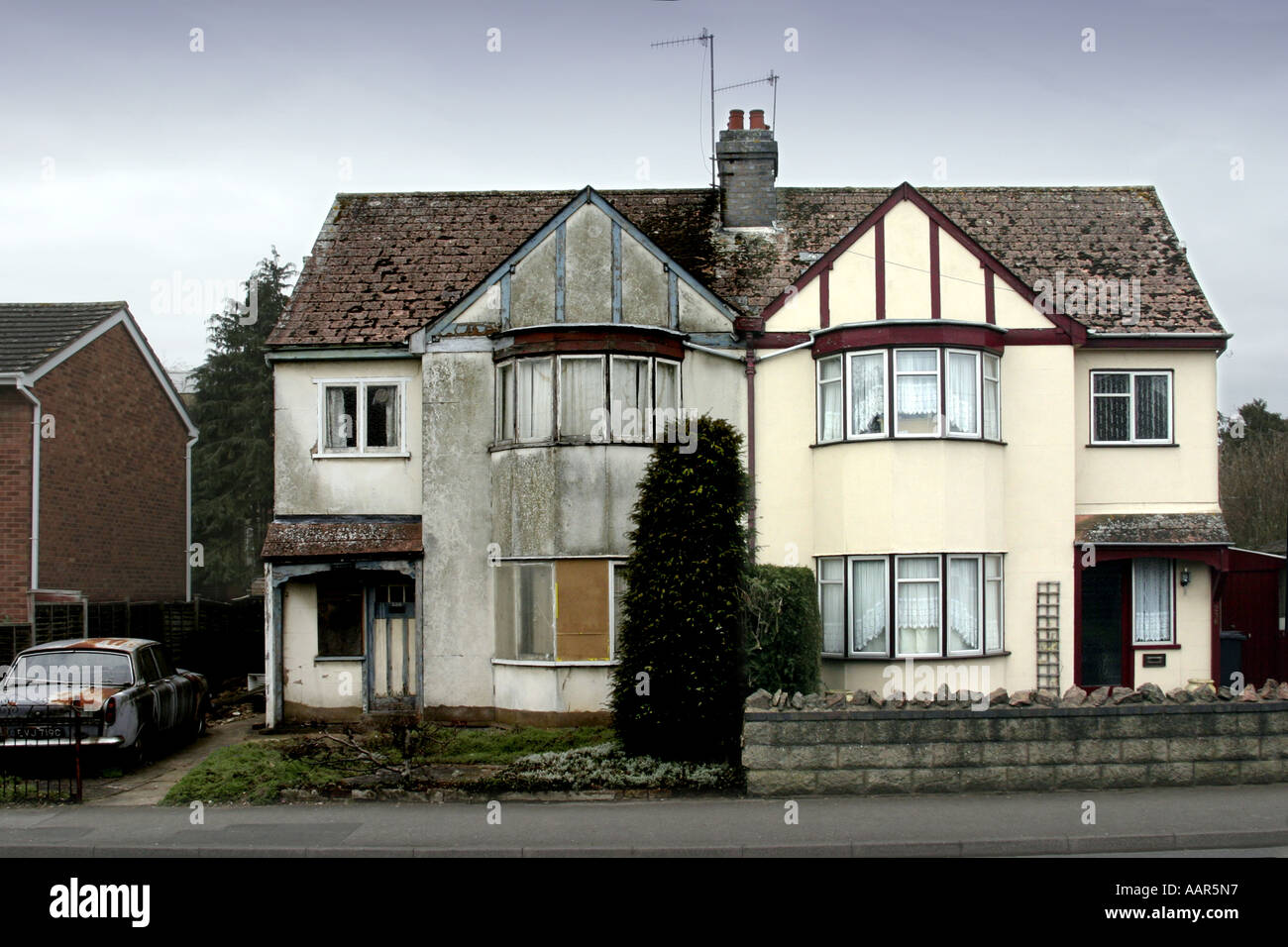 two semi-detached houses. one in good order the other dilapidated - Stock Image