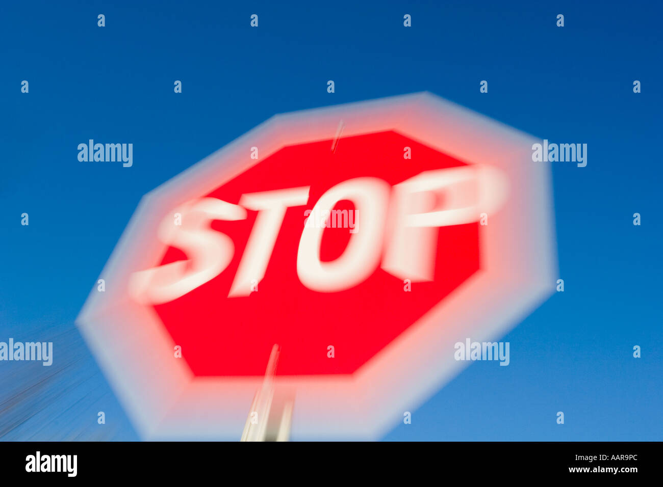 Stop sign in bright red and white against sunny blue sky - Stock Image