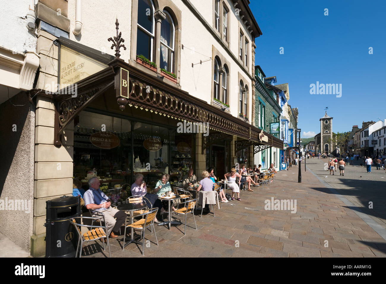 Cafe in the town centre with Moot Hall in the background, Keswick, Lake District, Cumbria, England, UK - Stock Image