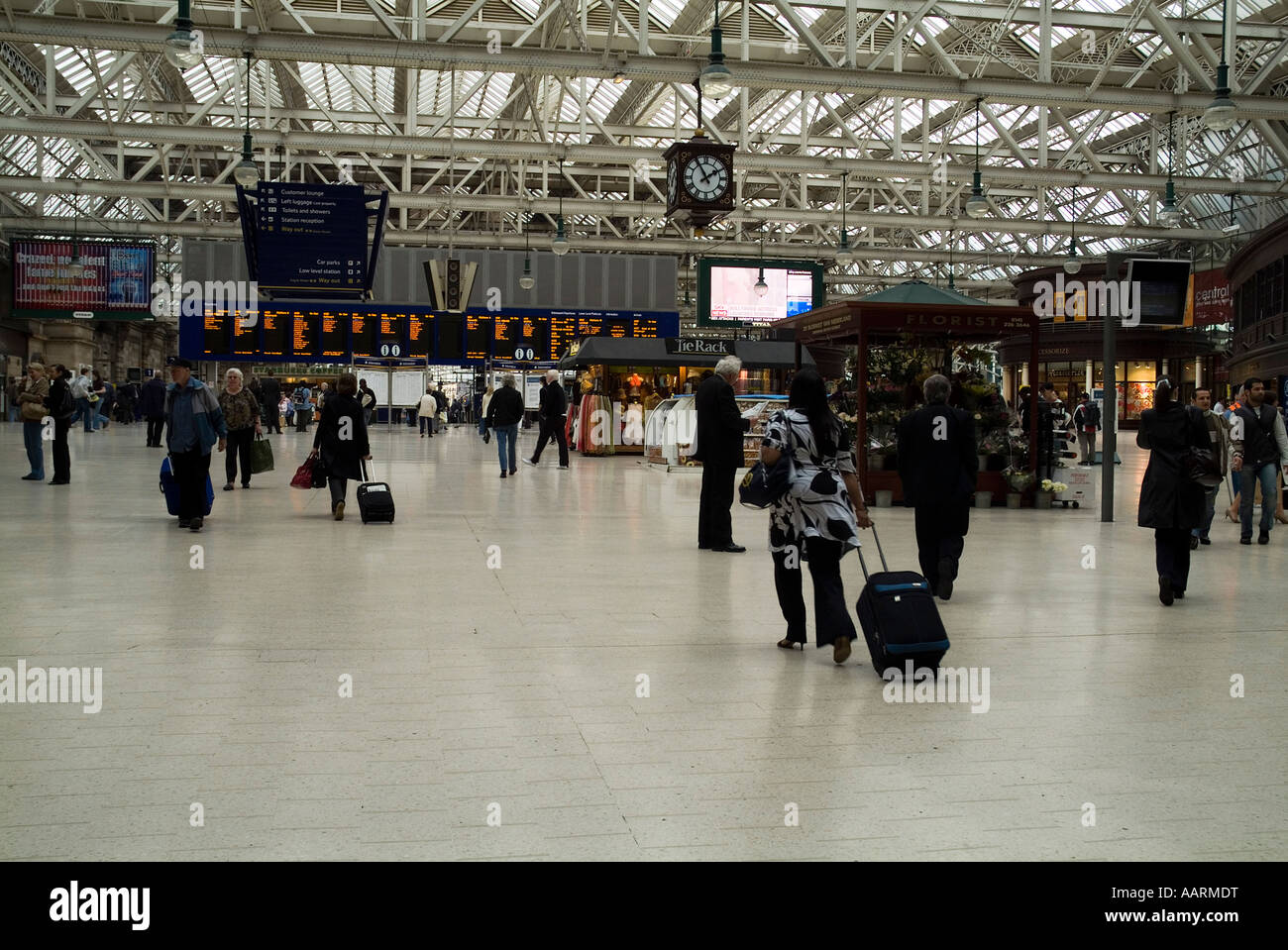 dh  CENTRAL STATION GLASGOW Passengers arriving with suitcases at train timetable board railway travel - Stock Image