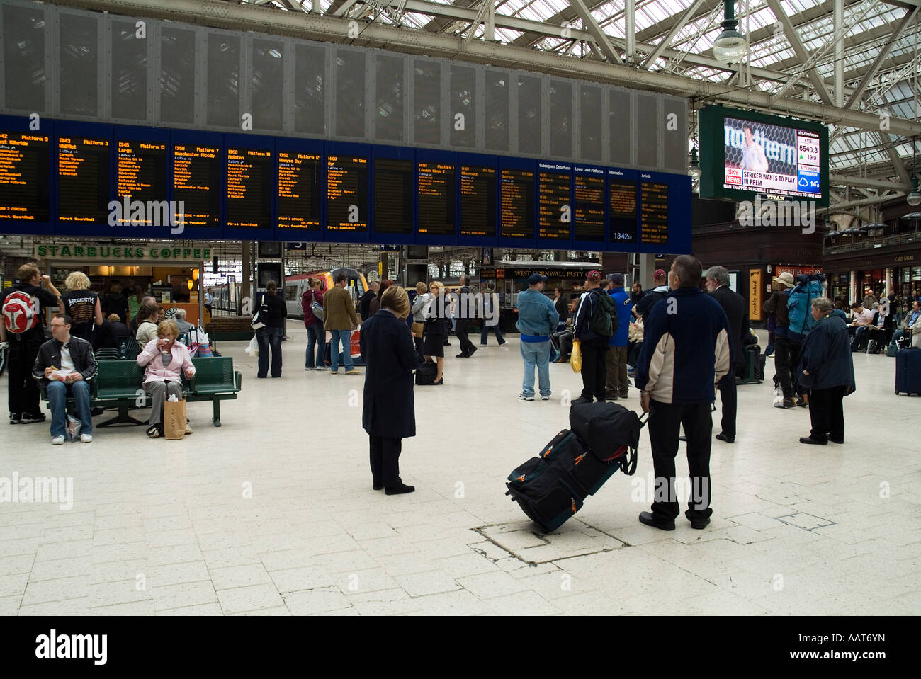 dh  CENTRAL STATION GLASGOW Passengers looking at train timetable board departure scotland railway busy - Stock Image