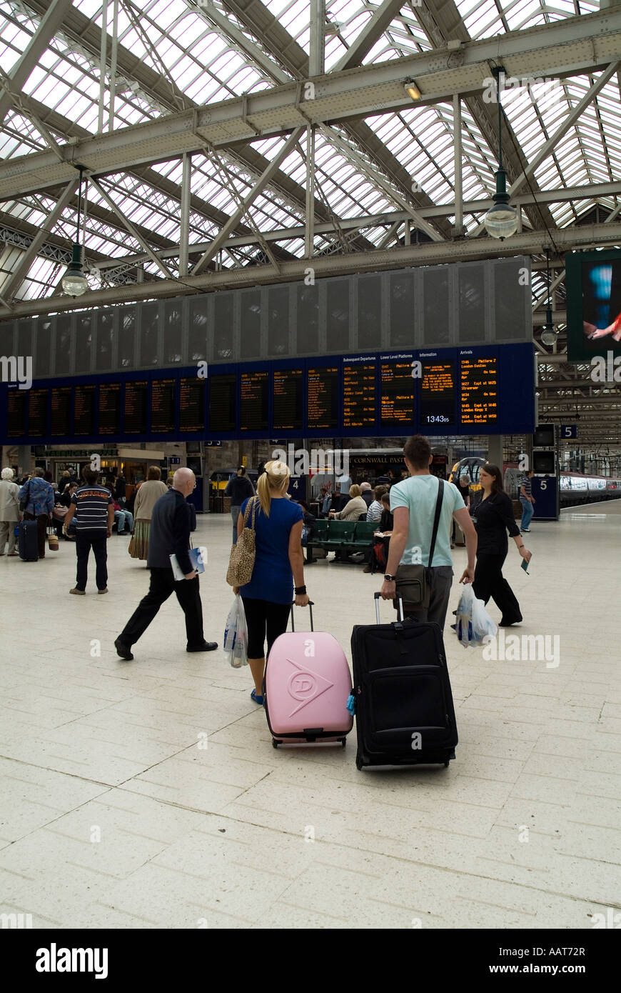 dh  CENTRAL STATION GLASGOW Passenger couple with suitcases looking at train timetable board - Stock Image