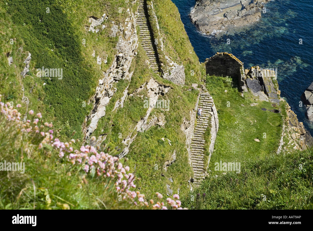 dh North coast 500 WHALIGOE CAITHNESS Man walking down steep stone steps to cove fishing harbour carved out of seacliff scotland tourist Stock Photo