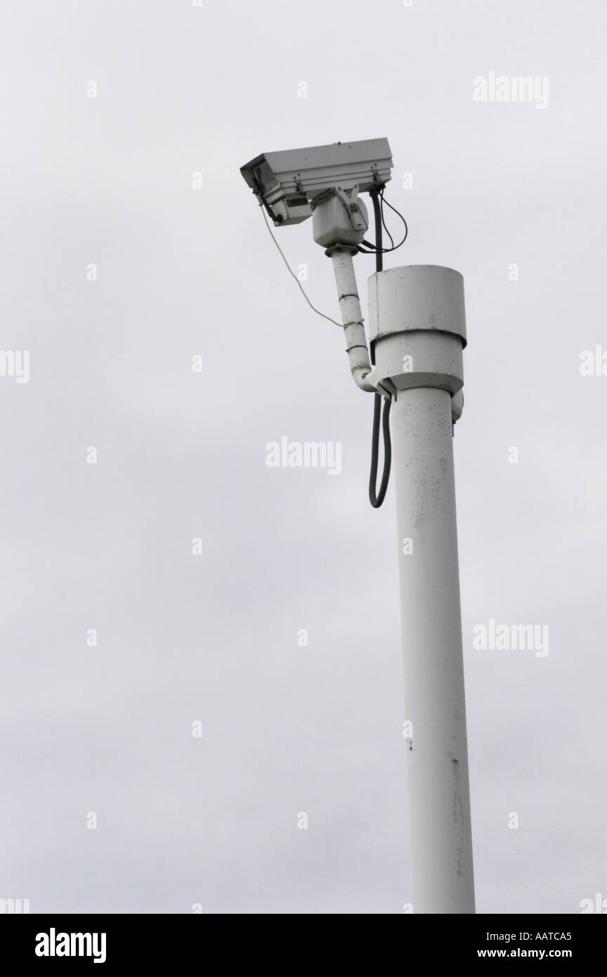 security camera against a pale sky - Stock Image