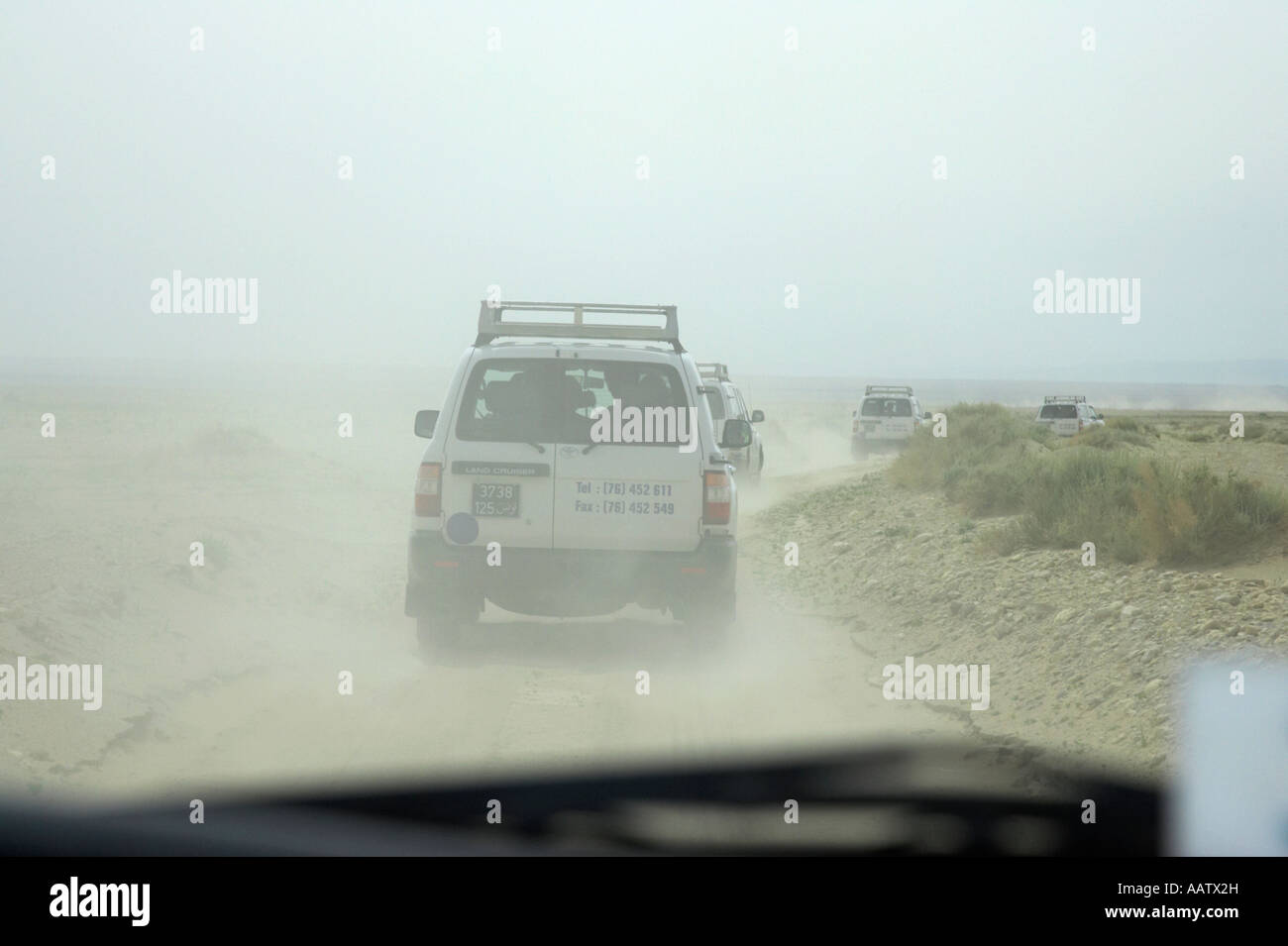 in a convoy of off road vehicles driving through dusty desert in Tunisia Stock Photo