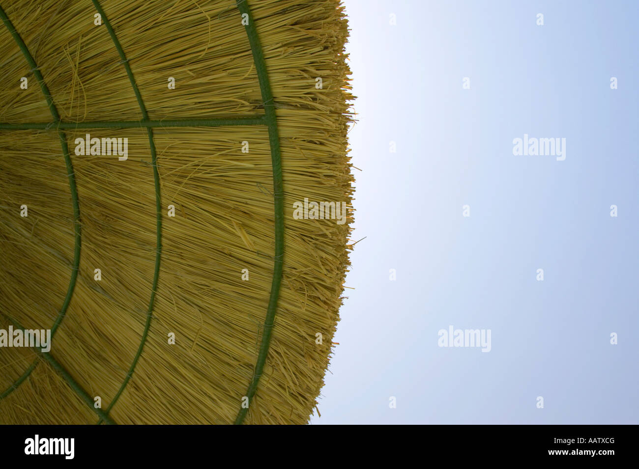edge of straw parasol protecting against harmful UV rays from the sun blue sky - Stock Image