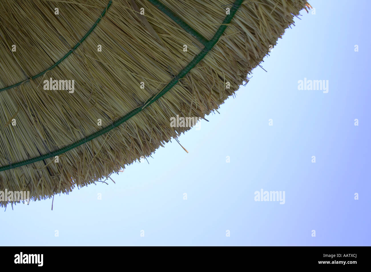 straw parasol protecting against harmful UV rays from the sun with blue cloudless sky - Stock Image