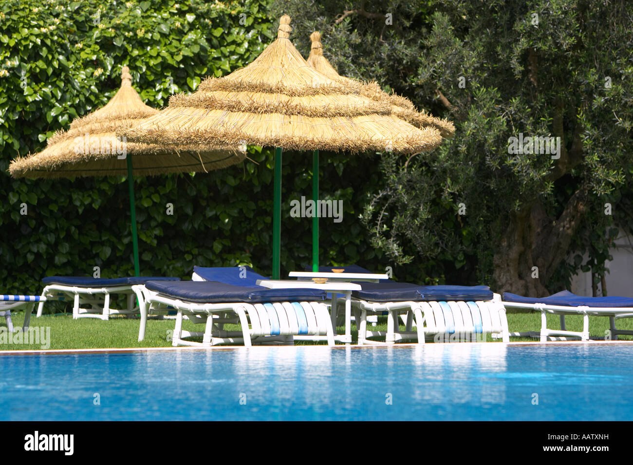 sun loungers and straw protective parasols by the pool in a resort hotel hammamet tunisia - Stock Image