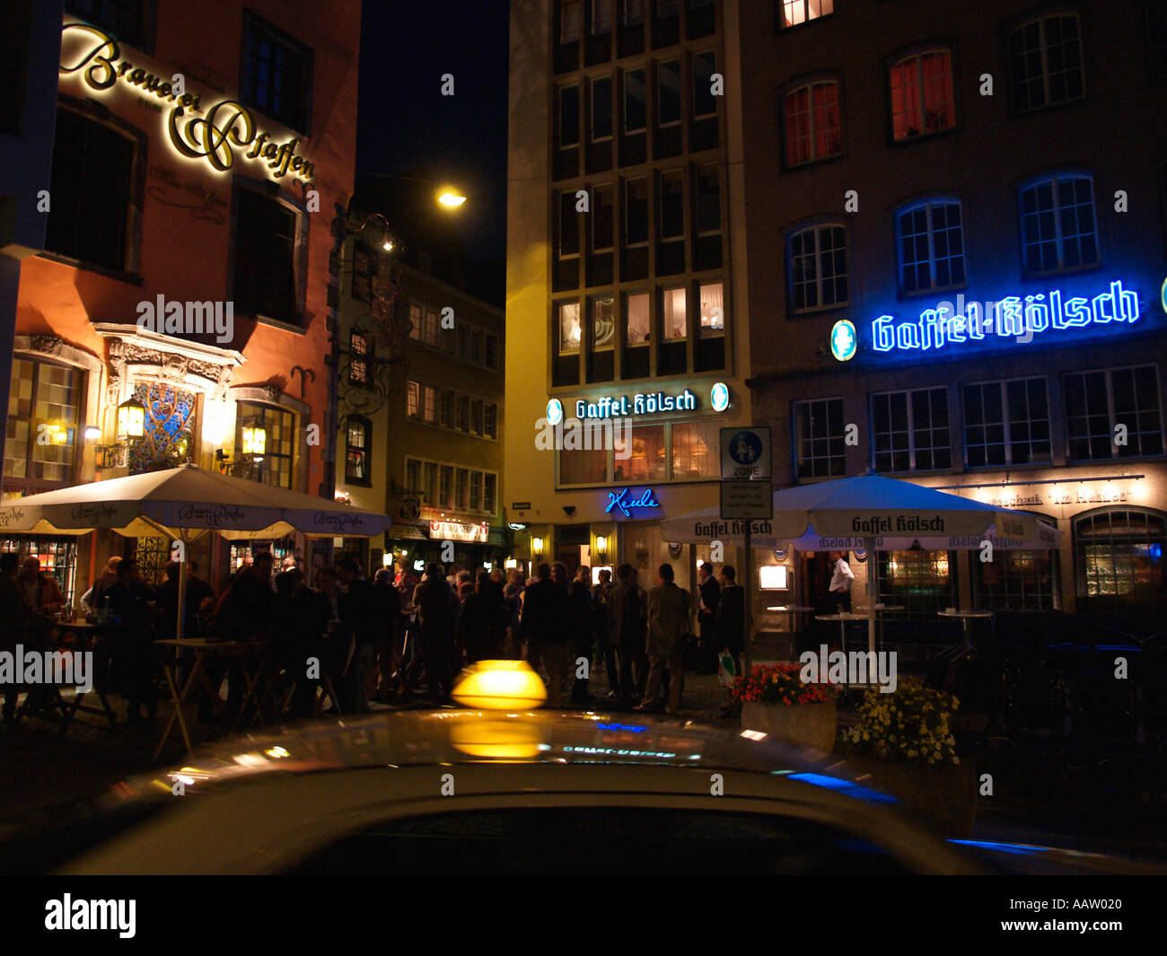 busy nightlife scene on the streets of cologne with a taxi passing the typical german biergartens cologne germany