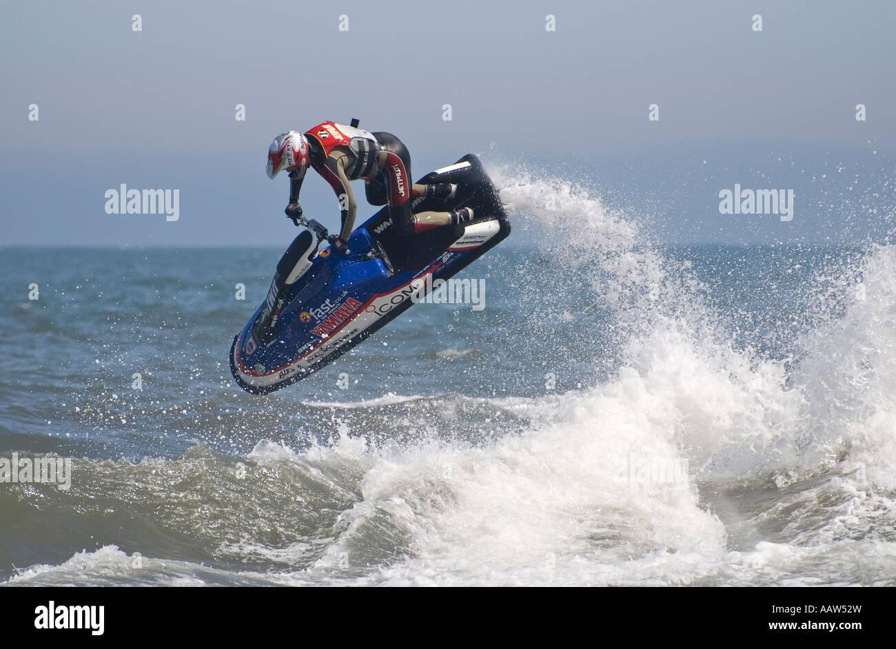 Jet skier performing jump on sea - Stock Image