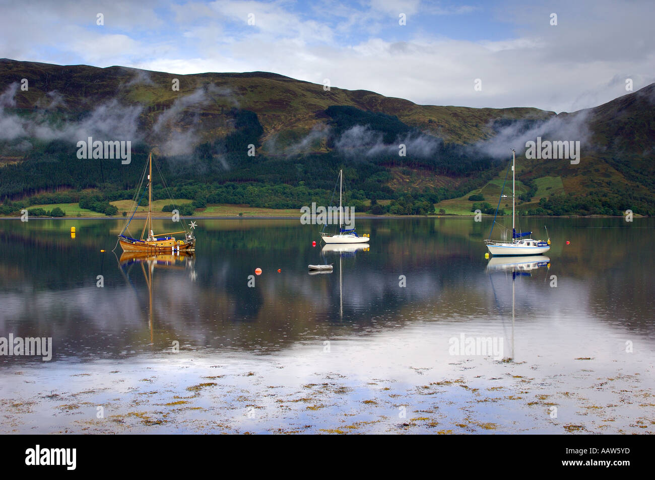 Three sailing boats on Loch Loch Leven near Ballachulish Glencoe with light clouds drifting by the mountainous backdrop Stock Photo
