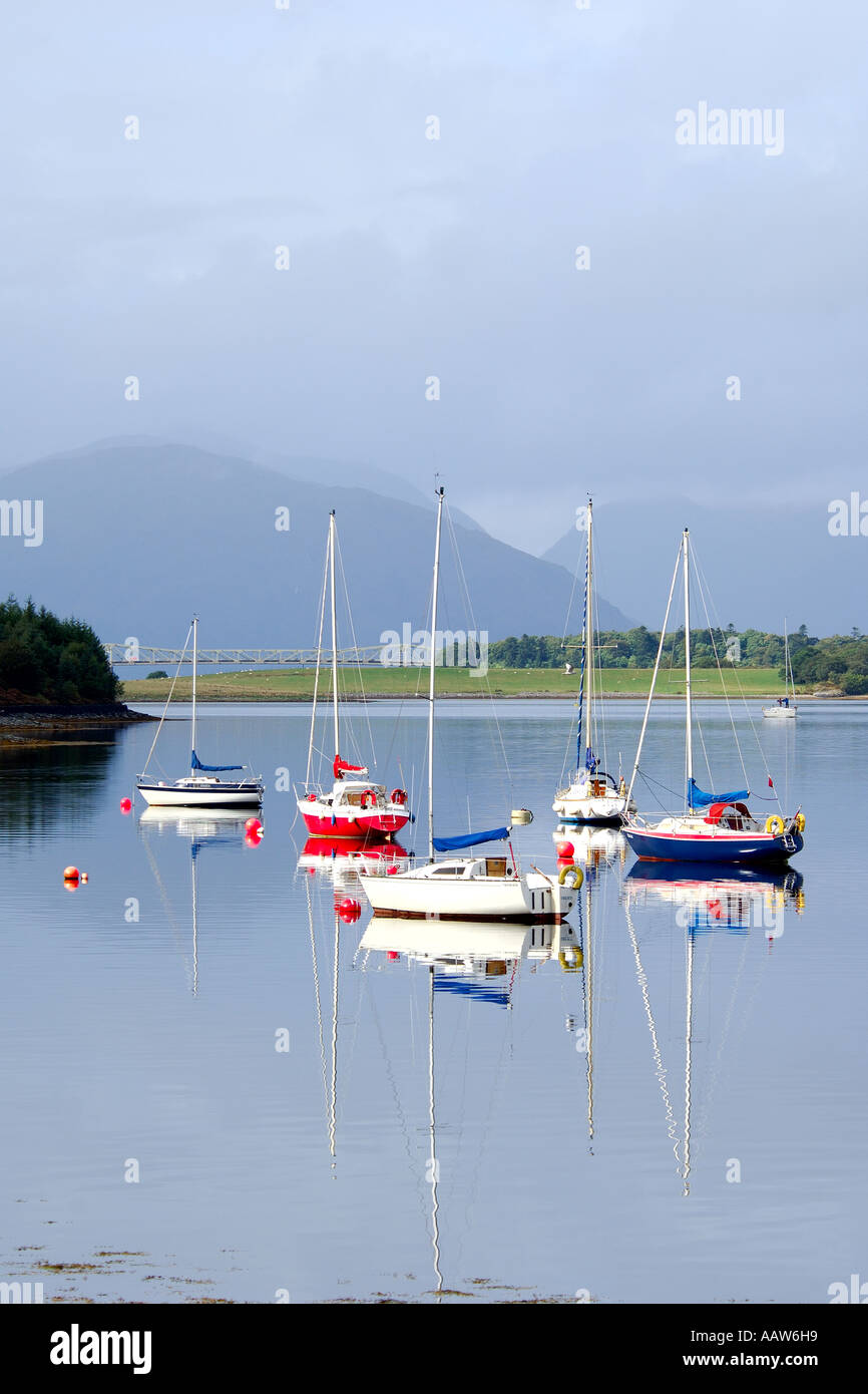 Five sailing boats on Loch Leven near Ballachulish Glencoe with road bridge and mountainous backdrop Stock Photo