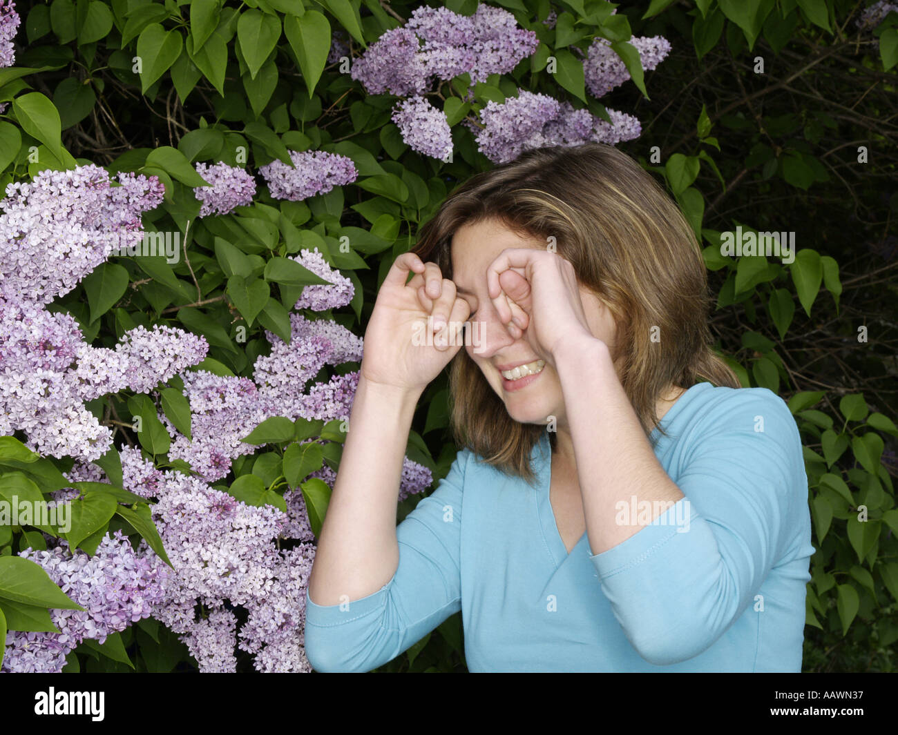 young woman teenager rubs her eyes in front of lilac in bloom - Stock Image