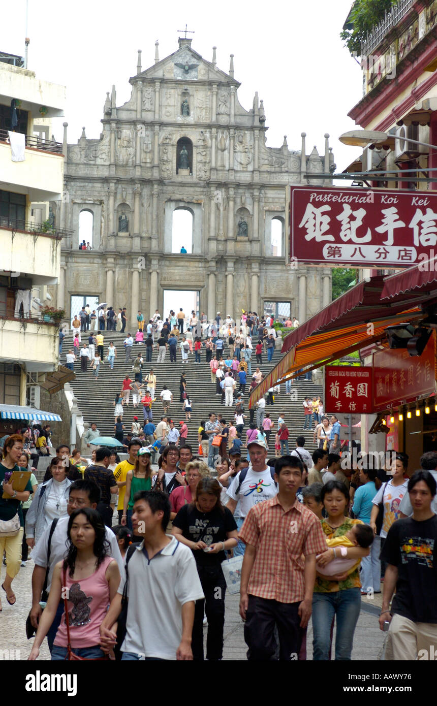 The famous facade of St Pauls Church and busy street in Macau China - Stock Image