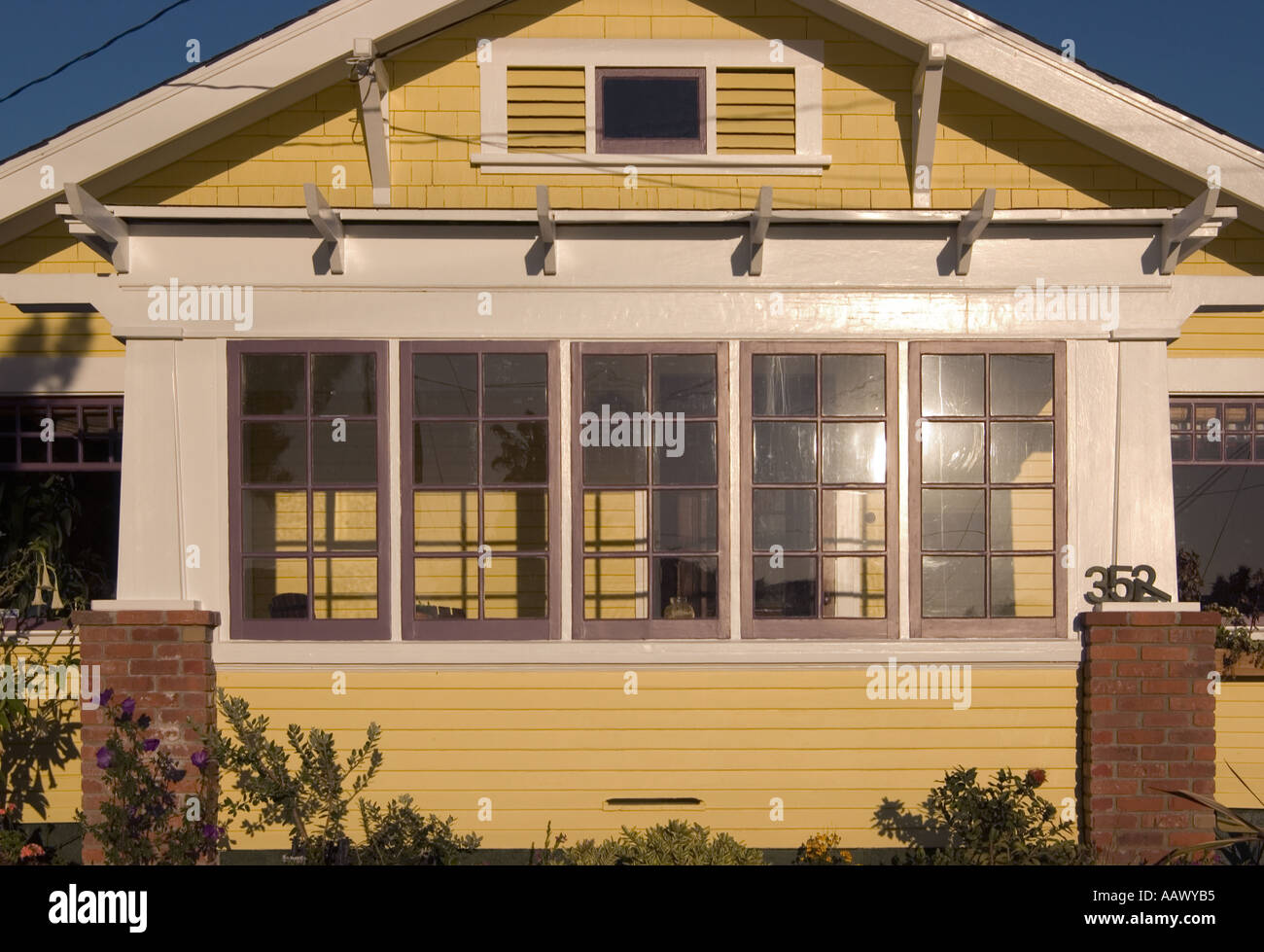 A color horizontal photo of a yellow Craftsman Bungalow style house