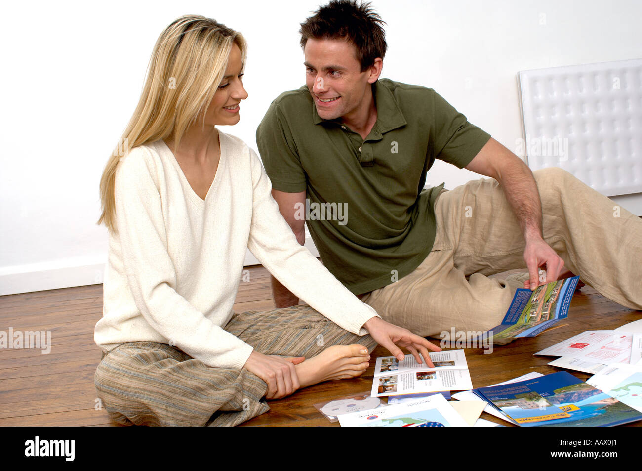 couple choosing from holiday brochures looking at holiday brochures planning a holiday - Stock Image