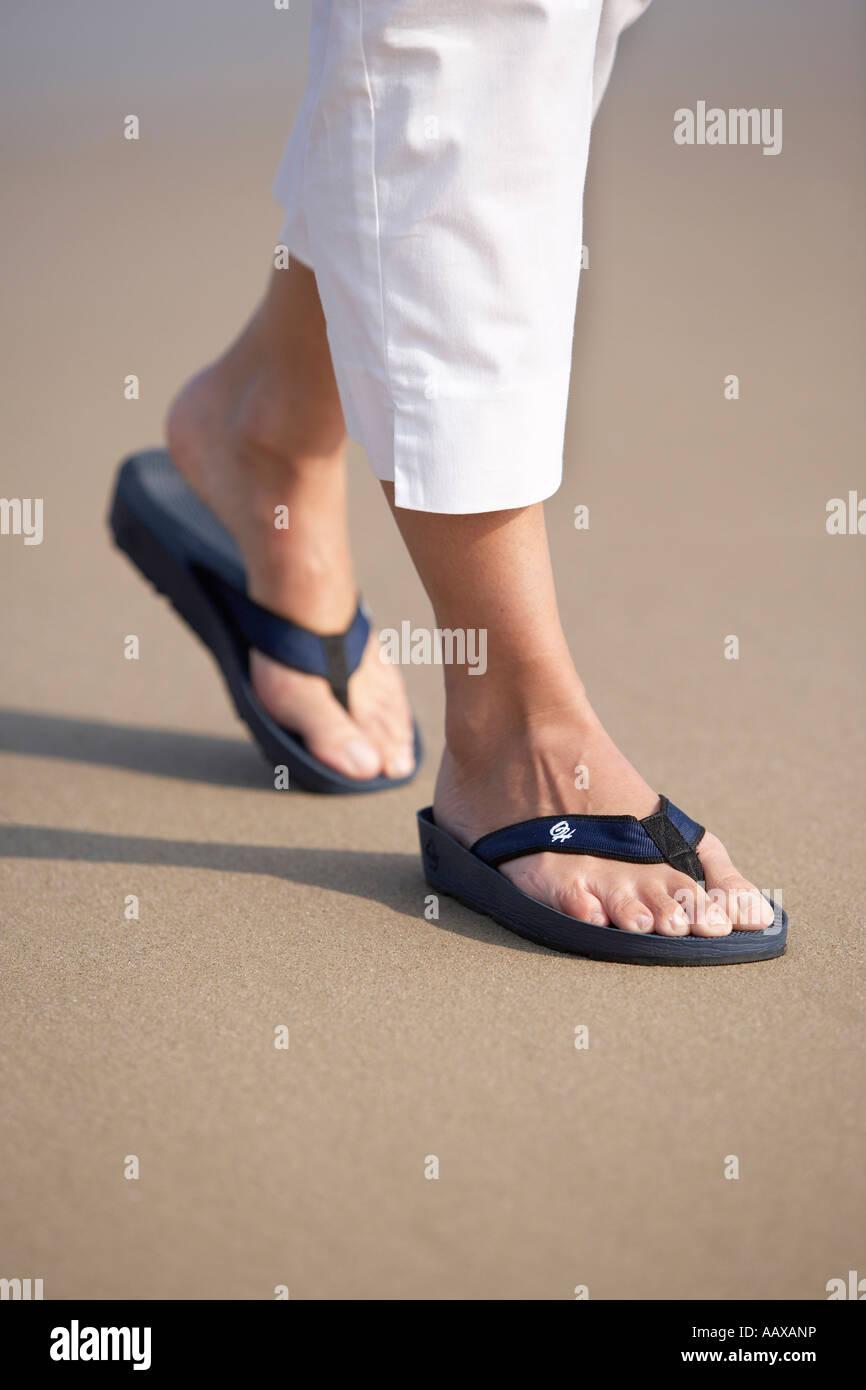 80685f922 Female 20 s 30s feet walking on sandy beach wearing Flip Flops Stock ...