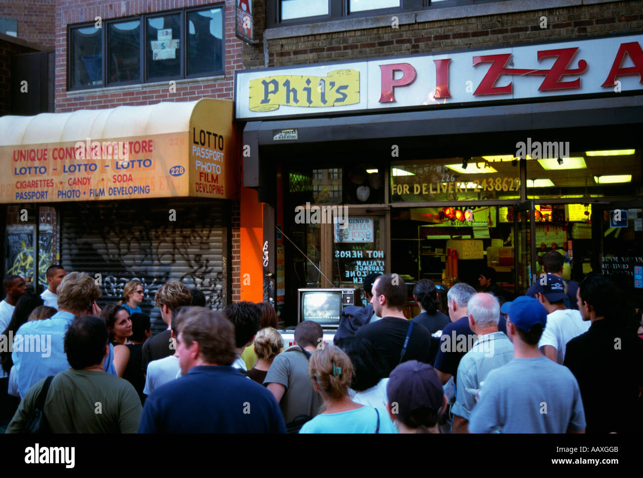 Crowds of people standing on the street watching news broadcasts on 9/11/2001 in NYC looking for information. - Stock Image