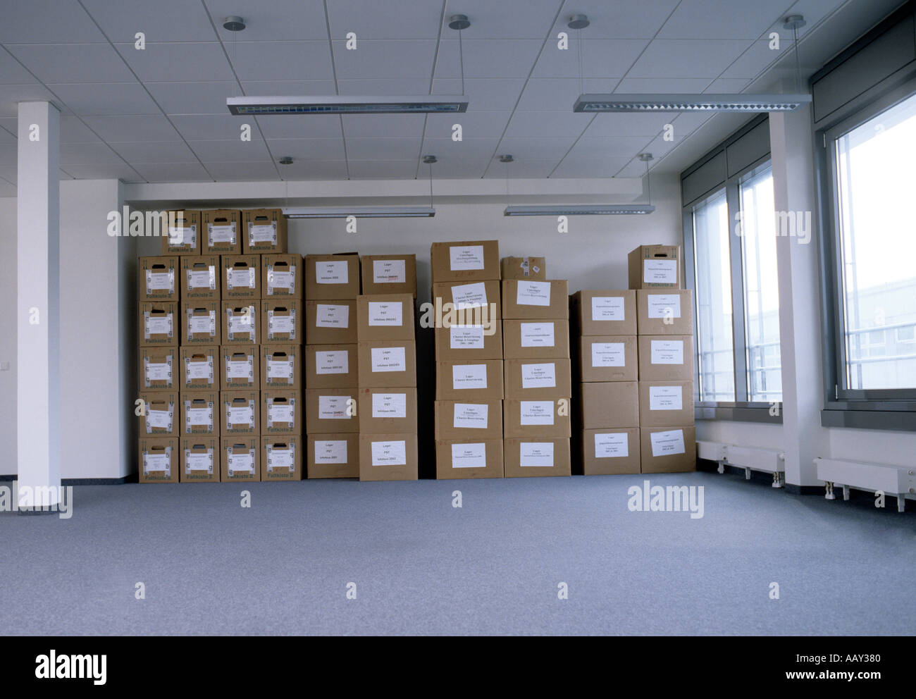 Empty Office Space With Neatly Stacked Cardboard Boxes In Background