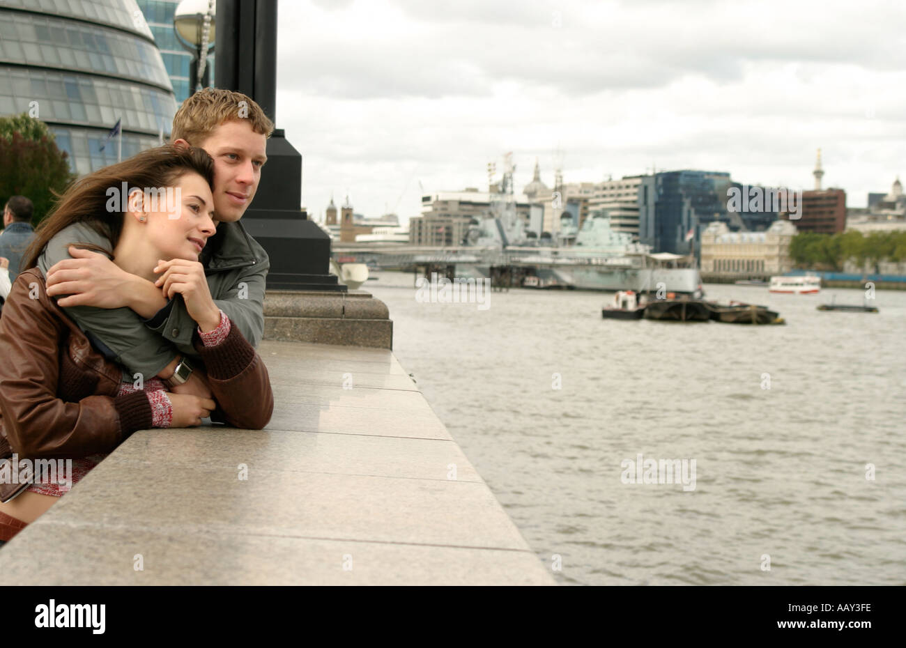 Young couple beside the River Thames in London England - Stock Image