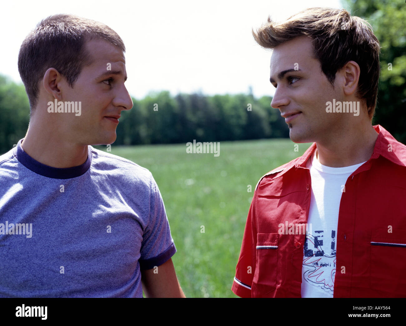 two gay men holding hands and looking at each other Stock