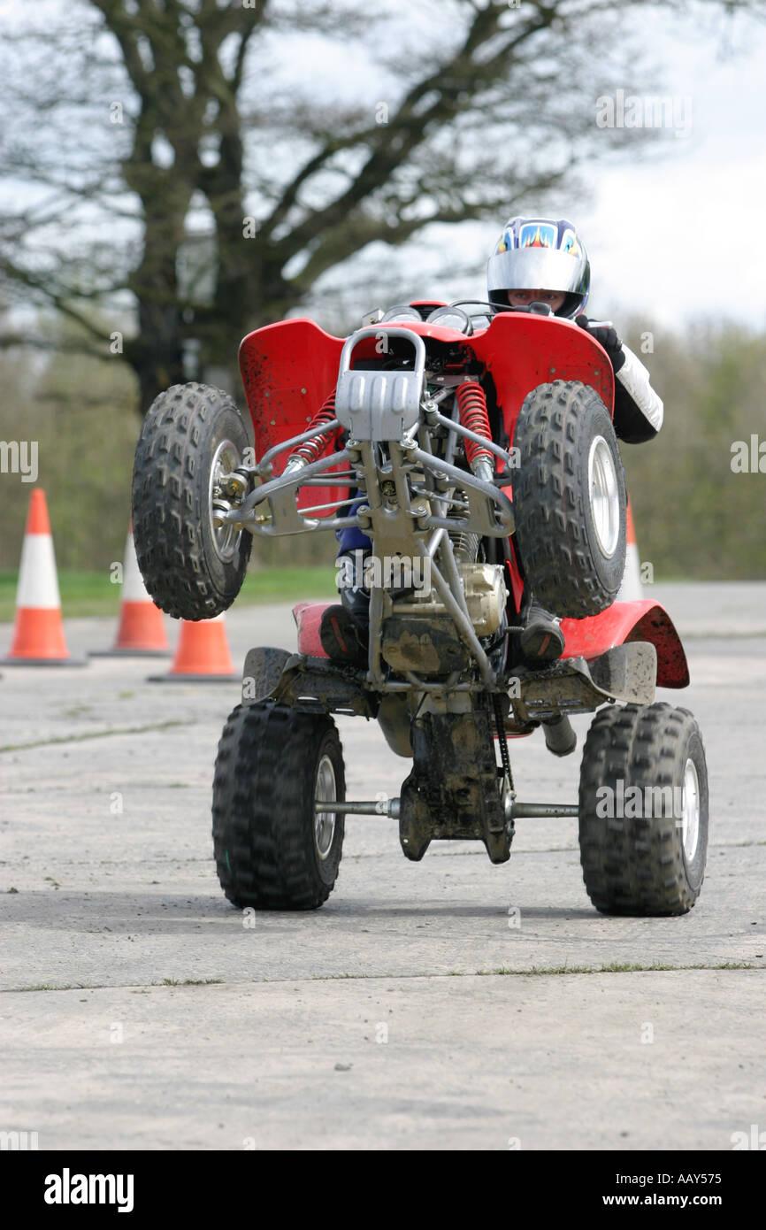 A stuntman wheelies a quadbike - Stock Image