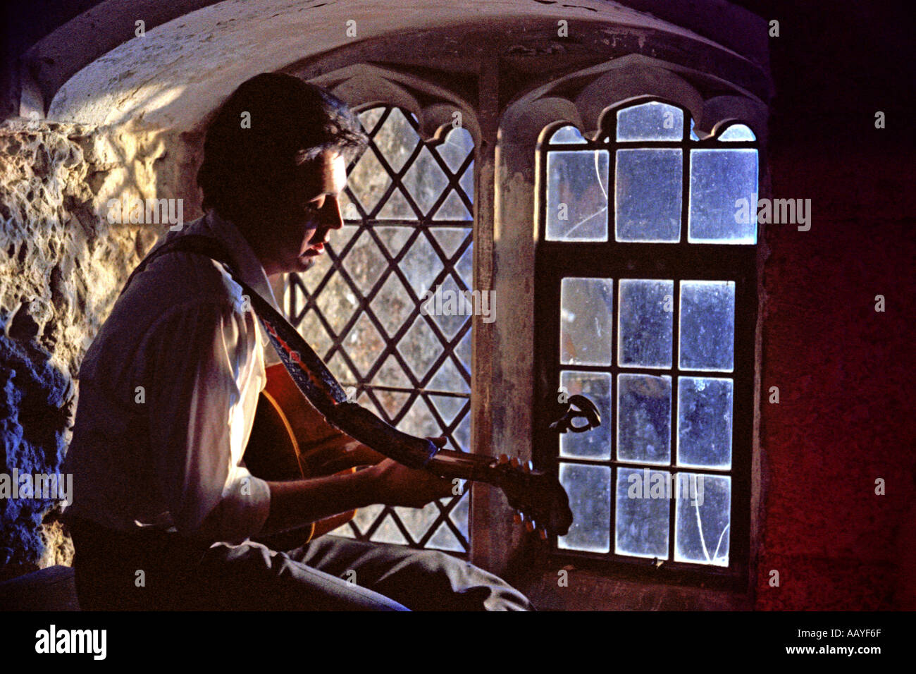 Paul McCartney seated in old castle window at night playing